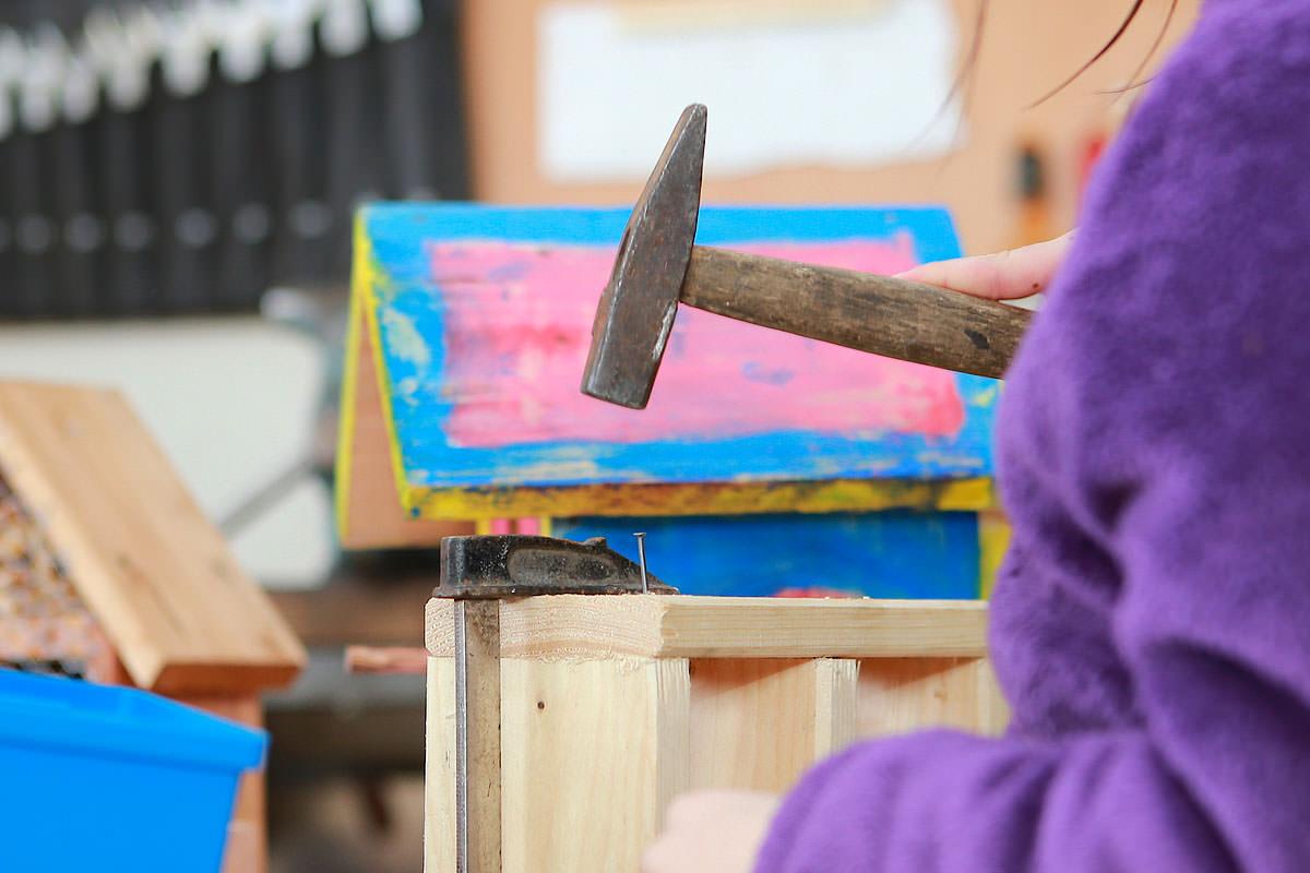 Kind beim Einklopfen eines Nagels mit einem Hammer in der Holzwerkstatt für Kinder