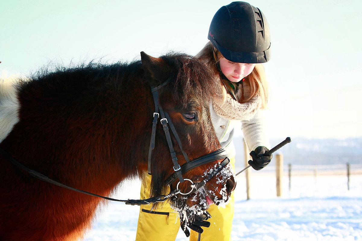 Kind mit Pony im Schnee